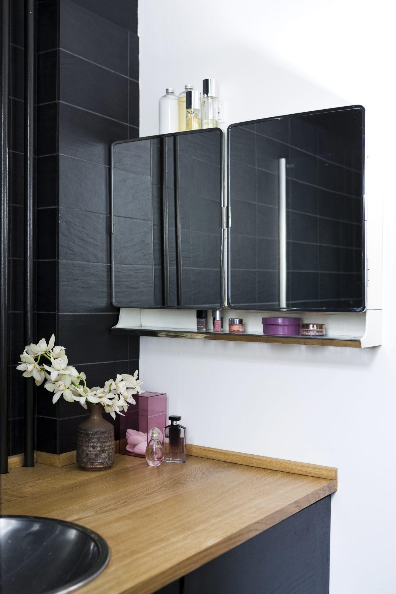 HVITT, SORT OG TREVERK: Badet er enkelt og rent med trebenk og svarte fliser mot en helhvit vegg. En Retrohylle med speildører henger på siden av benken. FOTO: Tia Borgsmidt