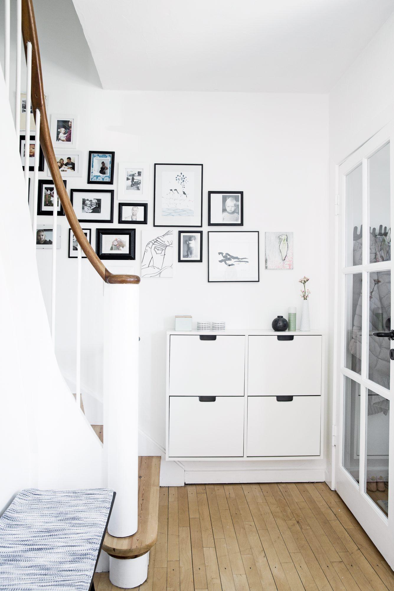 Gang og trappeløp med skoskap og bildevegg.