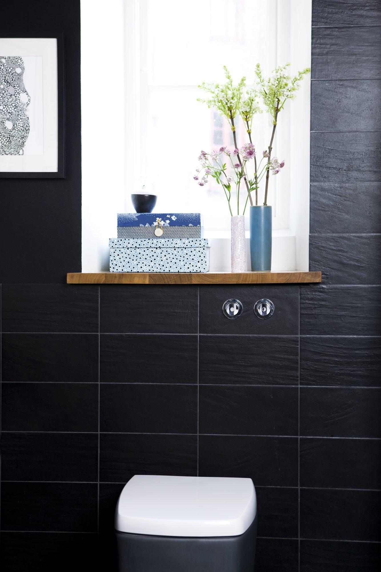 KONTRAST: Blomster i små vaser, og lekre esker i ulike farger tilfører litt femininitet til det maskuline badet. Toalettet er grått, og ses kun på grunn av sitt hvite lokk. FOTO: Tia Borgsmidt