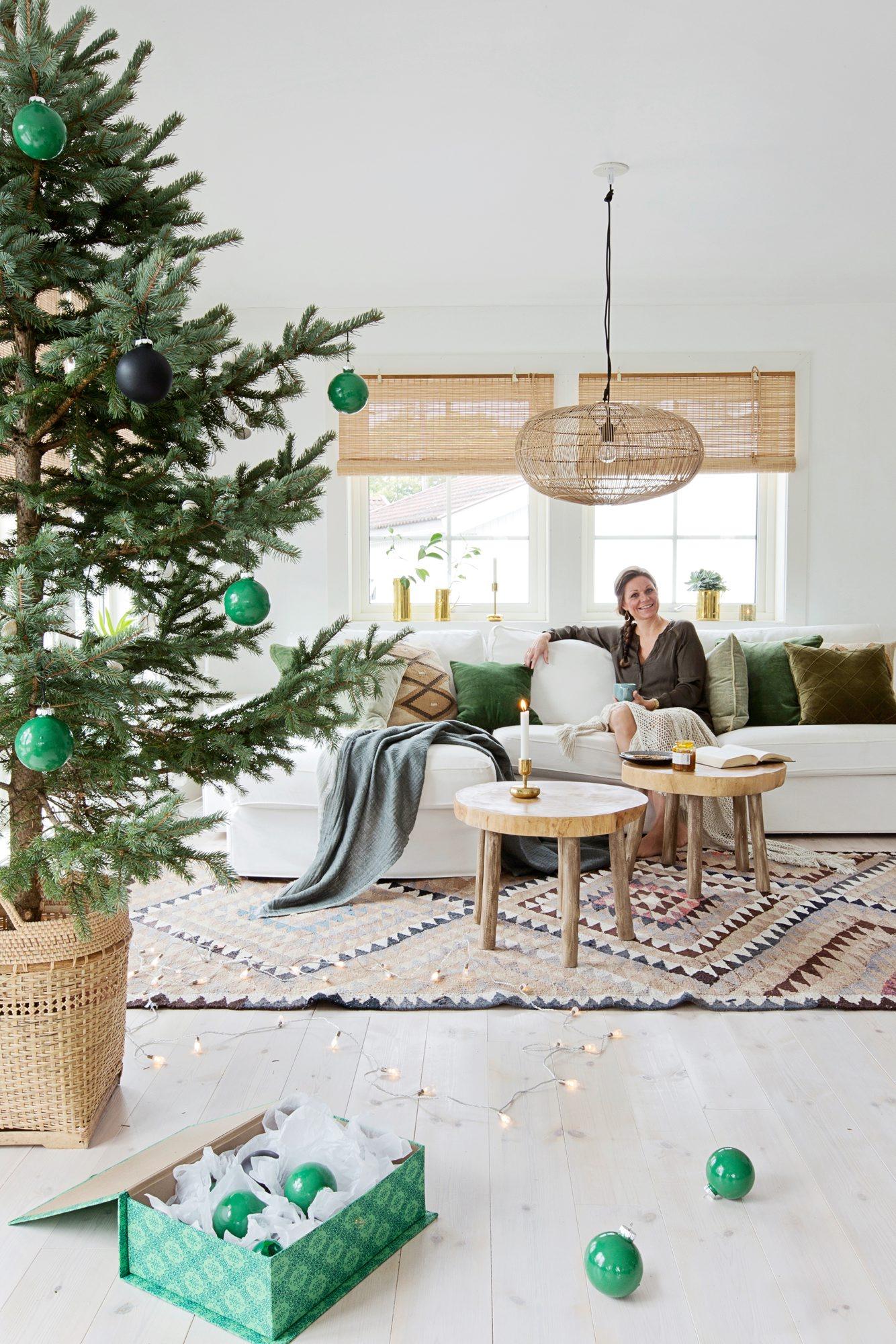 I sofaen fra Ikea ligger puter fra Ellos, Anouska og Kremmerhuset. Sofabordene er fra Palma, gulvteppet fra lauritz.com, og kurvlampen i taket fra Anouska. Messingstakene i vinduet er arvegods. Edelgranen er pyntet med grønn- og svartmalte julekuler. Treet står i en kurv fra Anouska. Den grønnmønstrete esken er fra Verket Interiør. FOTO: Jorunn Tharaldsen