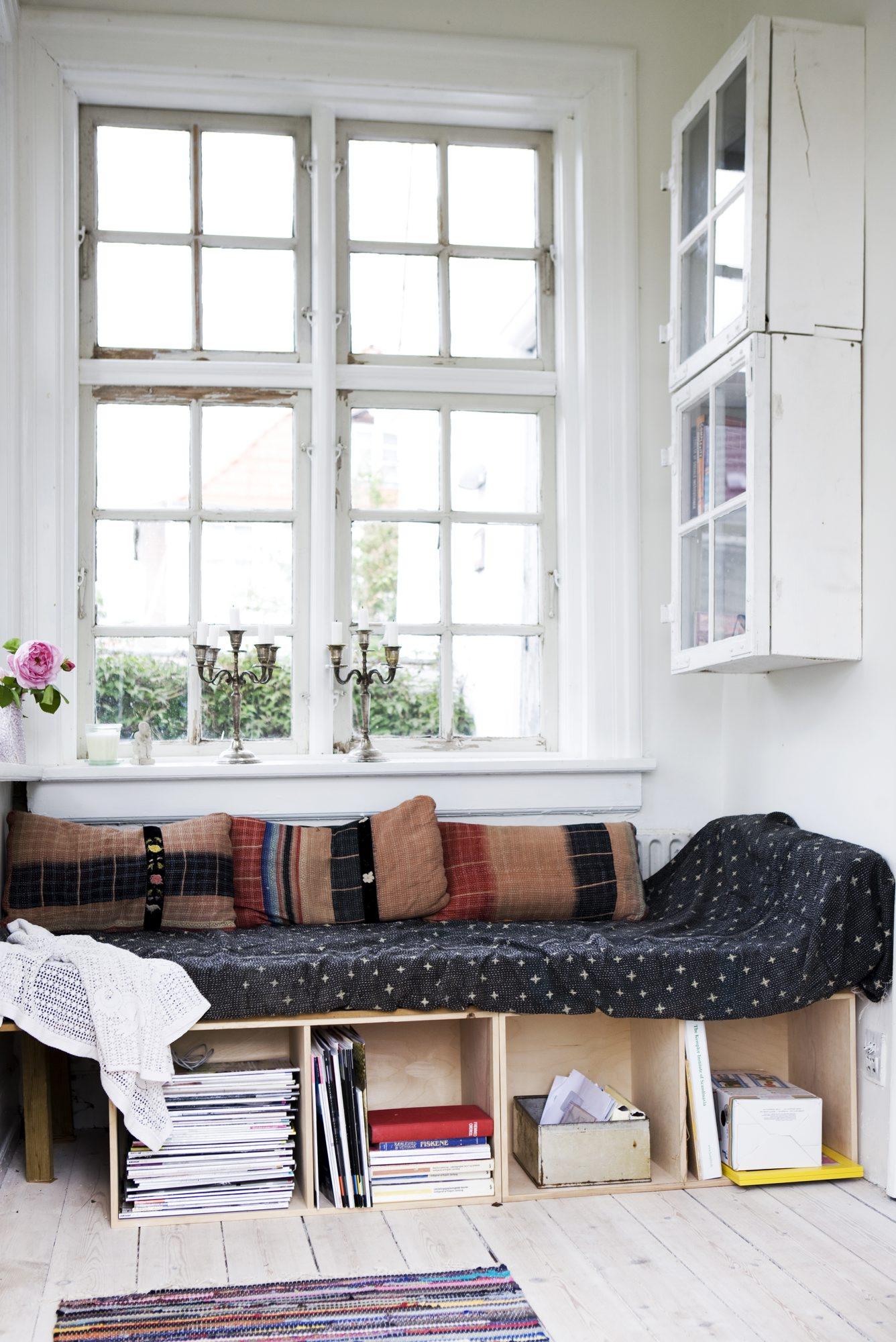 I husets entré er det god plass. Kassene under benken gir ekstra oppbevaring. Skapet på veggen består av malte kasser med gamle vinduer som dører.