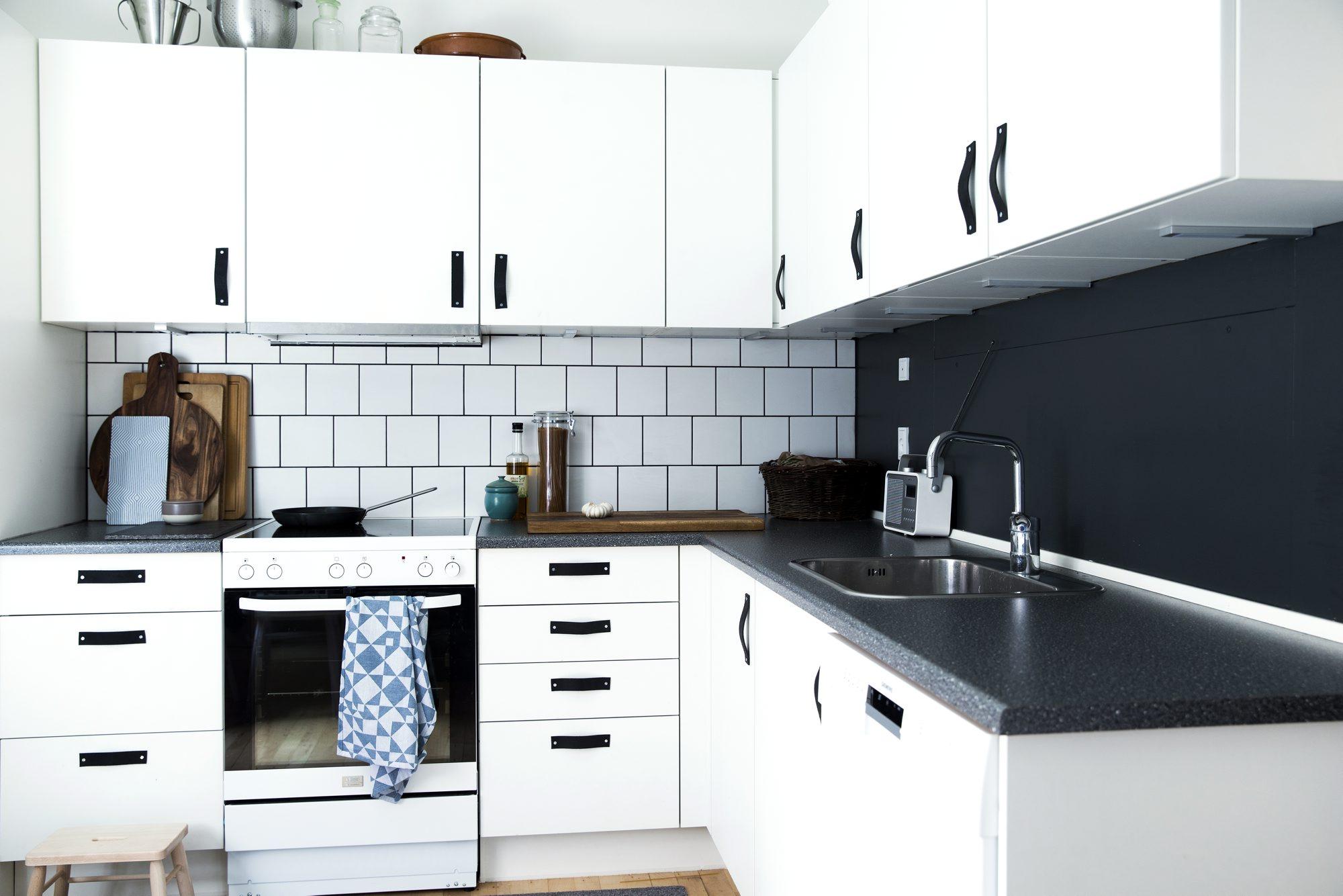 SLIPP KREATIVITETEN LØS: Stålplaten over komfyren ble erstattet av flisene Harmony fra Höganäs. De nøytrale stålhåndtakene ble skiftet ut med svarte lærhåndtak som beboeren laget selv. FOTO: Tia Borgsmidt