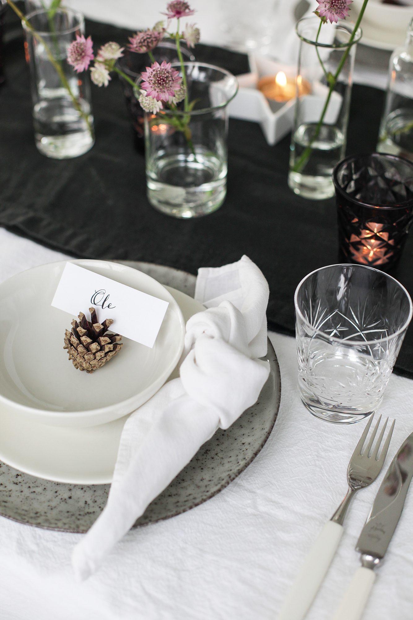 juledekket bord med kongle som bordkortholder