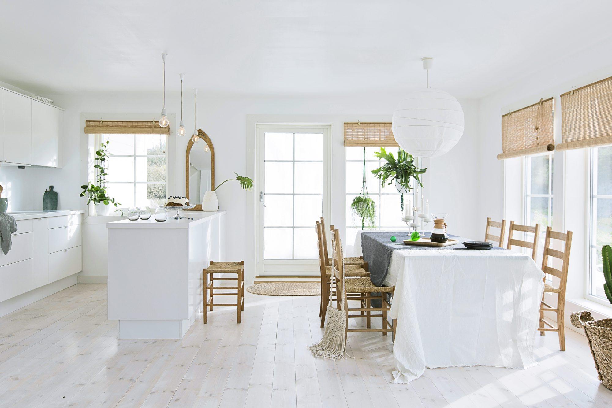 Kjøkkenet fra Ikea har hvite, matte overflater. Rullegardinet i bambus fås som bestillingsvare hos Bauhaus. Speilet har tilhørt Anettes mormor. Pendellampene er fra Nud. FOTO: Jorunn Tharaldsen