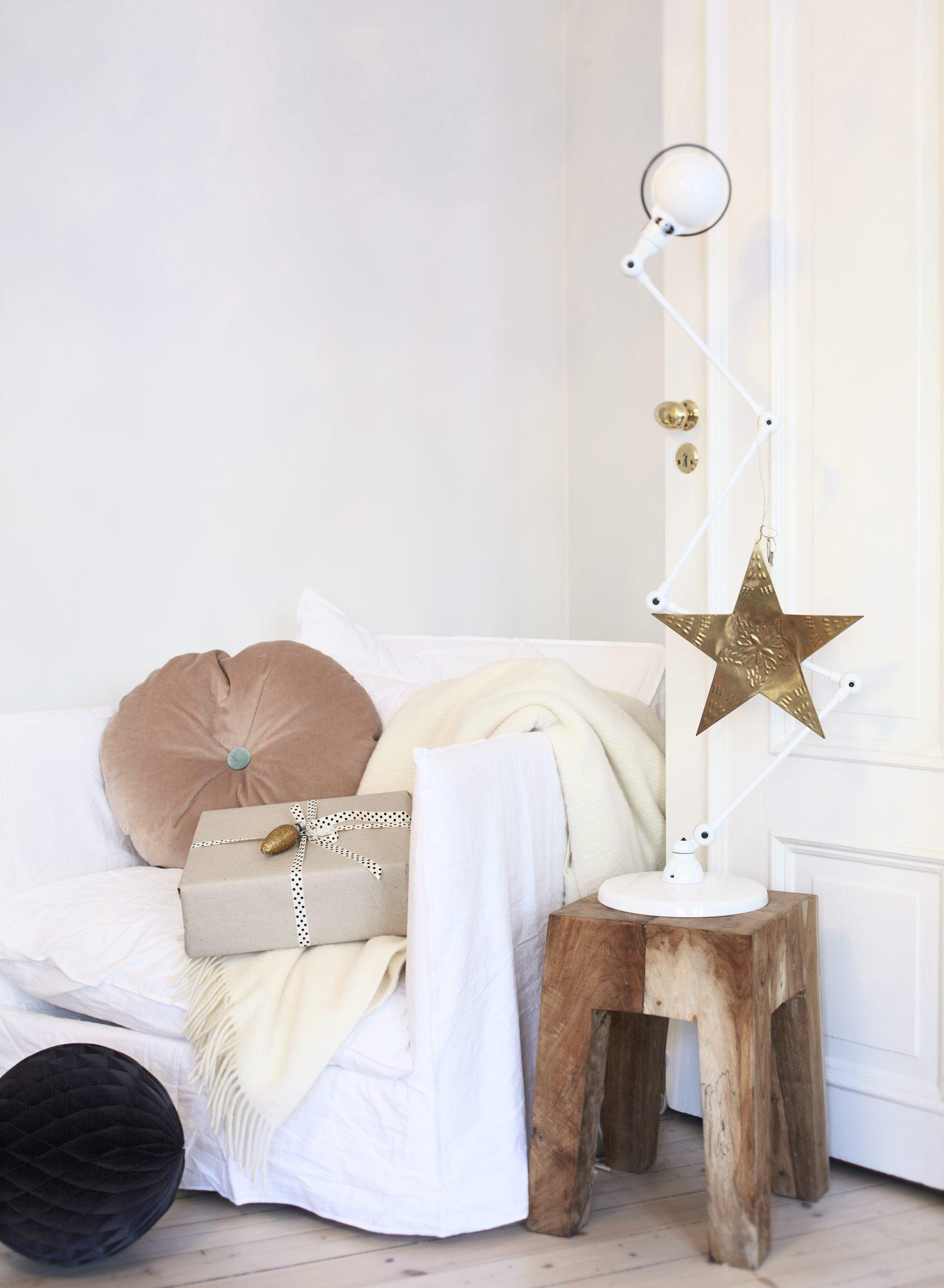 I den hvite Ghost-stolen fra Gervasoni ligger en velurpute fra Christina Lundsten/Muchi og et kremfarget ullpledd fra Åhléns. Papirballen er fra Bolina, og gavepapiret og båndet fra Panduro. På krakken fra Muubs står en Jielde-lampe fra Eske. Metallstjernen er fra Country Chic. FOTO: Margaret M. De Lange